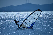 Female Windsurfer On The Water