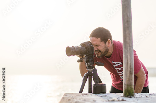 Fototapeta The photographer with the camera on a tripod. On a background the sea and rocks obraz
