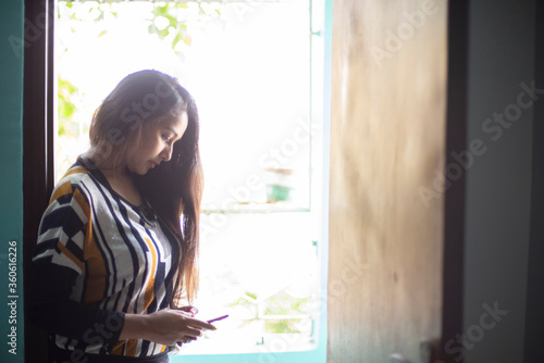 An Indian Bengali beautiful and young girl in western dress standing in front of a balcony with ample light while leaning on a door frame watching her cellphone Canvas Print