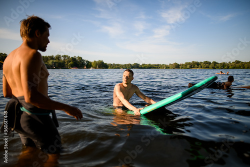 Fototapeta man sits on a surf board in the water and listens to the trainer obraz