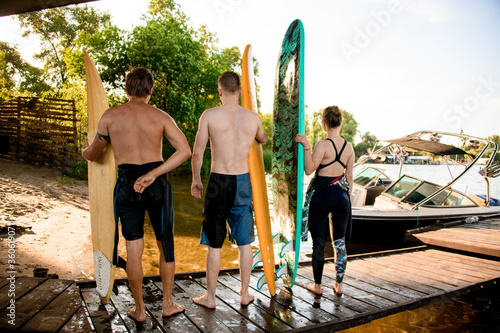 Fotomural Rear view of group of people with boards for surfing in their hands
