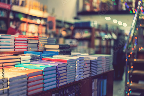 lot of new books in hardcover. image of Abstract Blur people at book store in shopping mall for background usage. toned