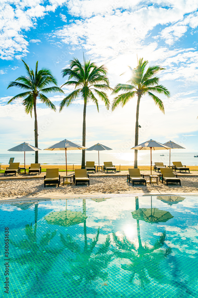 Fototapeta Beautiful luxury umbrella and chair around outdoor swimming pool in hotel and resort with coconut palm tree on blue sky