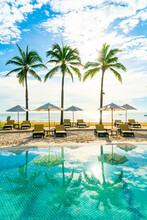 Beautiful Luxury Umbrella And Chair Around Outdoor Swimming Pool In Hotel And Resort With Coconut Palm Tree On Blue Sky