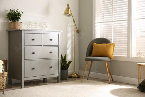 Fototapeta Grey chest of drawers in stylish room interior