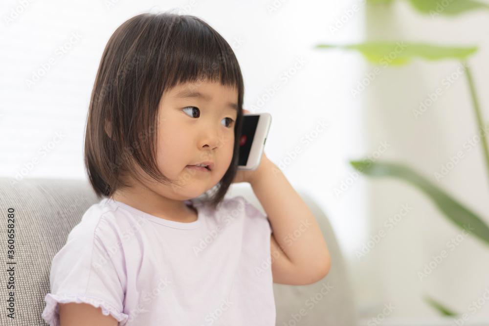 Fototapeta スマートフォンで電話をかける3歳の子供