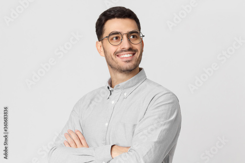 Obraz Portrait of young handsome smiling man dressed in shirt and eyeglasses, standing with arms crossed, looking away, isolated on gray background - fototapety do salonu