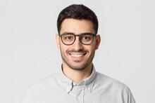 Eyewear Fashion. Headshot Portrait Of Handsome Smiling Man Dressed In Gray Shirt And Wearing Eyeglasses, Isolated On Studio Background