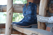 Cowboy Boots On A Wooden Fence
