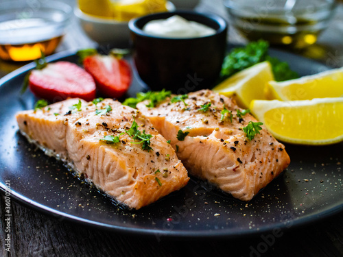 Fotomural Steamed salmon steaks with lemon, strawberries and creamy dip served on black pl