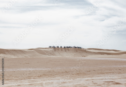 Dunes and barkhanes in the middle of the desert are and in the distance there is group of safari jeeps Wallpaper Mural