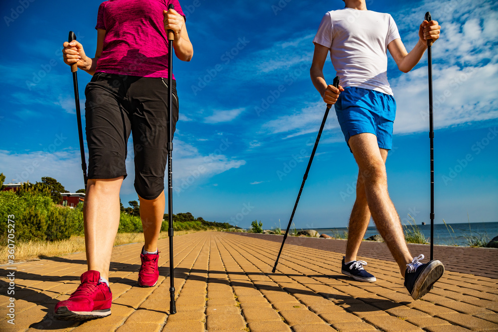 Fototapeta Nordic walking - middle-aged woman and young man training by the sea shore