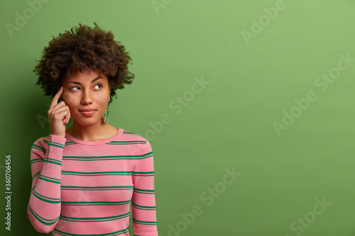 Fotografie, Tablou Half length shot of thoughtful dark skinned woman keeps fore finger on temple, thinks about offer or analyzes received information, dressed in striped jumper, poses against green background