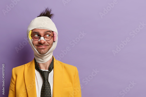 Fototapeta Funny businessman beaten by street outlaws stands injured with bruise under eye bandage over head wears yellow suit and black tie isolated on purple wall looks away with cheerful expression copy space obraz