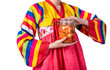 Leinwanddruck Bild - Korean woman is wearing a traditional hanbok, she holding a glass bottle containing Kimchi, which is the staple food for Korean people, On white isolated background.