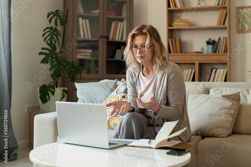 Middle aged female explaining something to online interlocutor during talk Canvas Print
