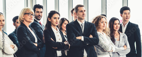 Fotografiet Successful business people standing together showing strong relationship of worker community