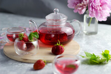 A Glass Teapot And Clear Mugs Stand On A Wooden Tray On A White Table. Inside The Teapot, Red Tea Is Brewed And Poured Into Mugs, Strawberries Are Lying Next To It