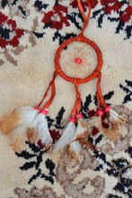 Vertical Shot Of A Red Dream Catcher Lying On A Carpet