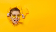 Horizontal Banner Of Young Girl In Glasses Tearing Paper And Peeking Out Hole, Curious About Commercial Offer On Copy Space On Right, Isolated On Yellow Background
