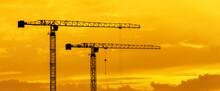 Construction Site With Cranes On Sunset Orange