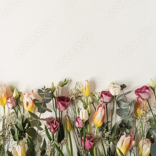 Obraz Flowers composition with many tulips, eucalyptus, wildflowers on white background. Flat lay, top view festive holiday celebration concept - fototapety do salonu