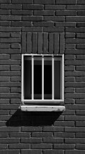 Vertical Greyscale Shot Of A White Window Lattice On The Cobblestone Wall