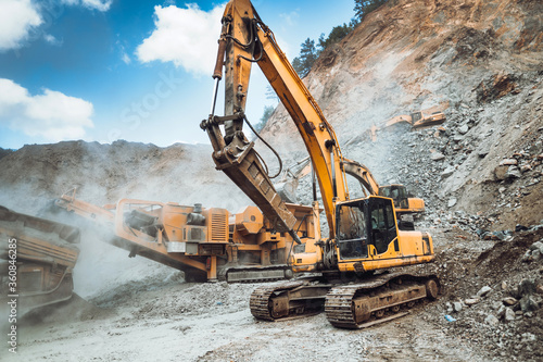 Fototapeta Industrial excavator loading ore and stone material from highway construction site into a dumper truck. obraz