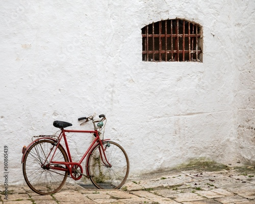 Fotomural Red bicycle leaned to a white building with a window with rusty balusters