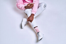 Cropped Shot Of A Guy Who Dressed In A Pink Hoodie, White Pants, Pink Socks And White Sneakers Holds A Phone. The Concept Of Gadgets, Accessories, Clothing And Lifestyle.
