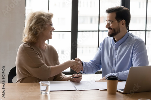 Smiling manager shaking mature businesswoman hand at meeting, business partners Wallpaper Mural
