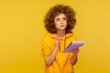 Portrait of pensive curly-haired hipster woman in urban style hoodie thinking over smart idea, holding pencil and notebook to write plans, to-do list. indoor studio shot isolated on yellow background