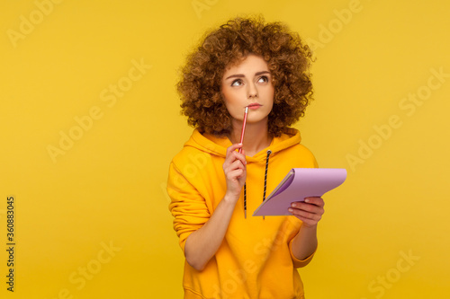 Fototapeta Portrait of pensive curly-haired hipster woman in urban style hoodie thinking over smart idea, holding pencil and notebook to write plans, to-do list