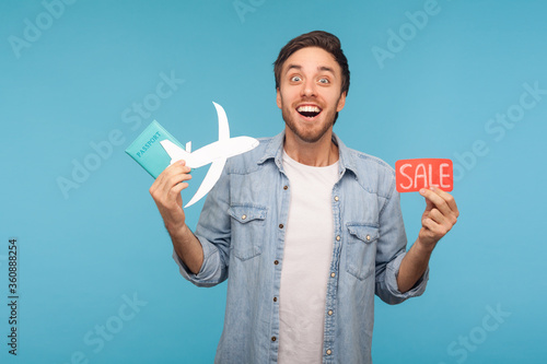 Fototapeta Portrait of amazed happy tourist man in denim shirt holding paper plane, passport and Sale word, planning vacation abroad with low cost air transportation. studio shot isolated on blue background obraz