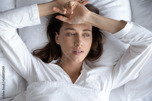 Obraz Top view of depressed sad young woman lie relax in bed look in distance thinking remembering, upset stressed millennial female rest in home bedroom feel sick suffer from illness or depression - fototapety do salonu