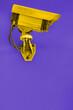Überwachungskamera in gelb vor einem lila Hintergrund