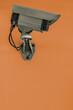 graue Überwachungskamera vor bräunlichem Hintergrund