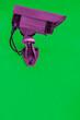 Überwachungskamera in lila vor einer grünen Wand