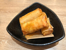 Deep Fried Spring Rolls Serving On Black Plate, Classic Snack Food Made With Ground Pork, Matchstick Cut Carrots, Sliced Cabbage And Thinly Sliced Onion All Wrapped Up And Fried Until Golden