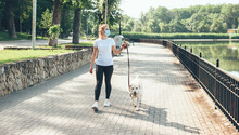 Full Sized Photo Of A Caucasian Woman With Blonde Hair And Medical Mask On Face Walking With Her Golden Dog