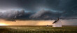 canvas print picture - Old church in the rural countryside with a sever storm at sunset. There is an outhouse visible in the scene as well as a green and yellow grass meadow.