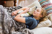 14 Year Old Girl Lying On Sofa Embracing Her English Cream Golden Retriever