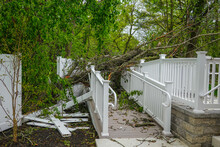 Damage To A White Metal Fence And Guard Rail Of A Deck And Ramp From A Tree That Fell During A Storm