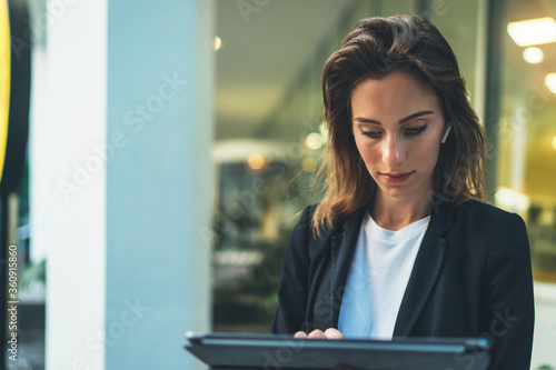 Fotografía Lifestyle business woman using tablet walking in evening city, girl banker dress
