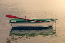White Wooden Fishing Boat Moored On The Shore At Sunset