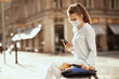 woman in blue blouse using smartphone app outdoors in city