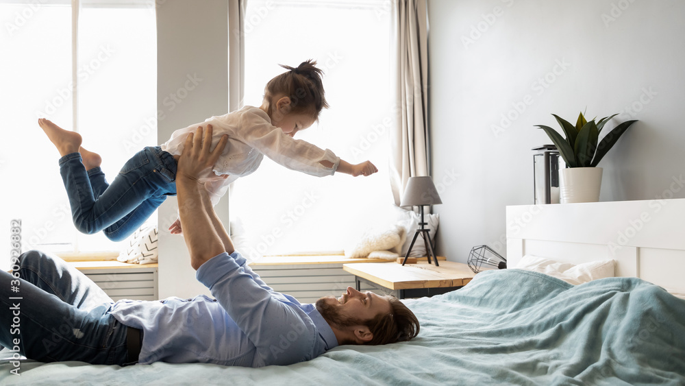 Fototapeta Smiling father holding little girl with hands outstretched pretending flying, relaxing in cozy bed in bedroom, happy young dad and adorable preschool daughter playing funny game in bedroom