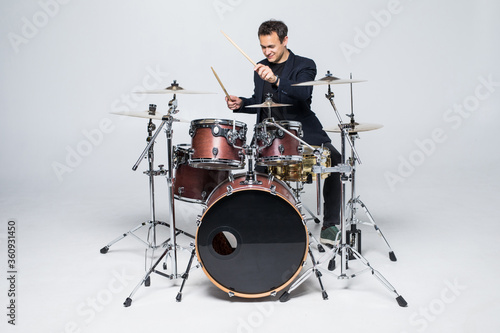 Tela Young attractive man drummer playing drums and cymbals isolated on white backgro