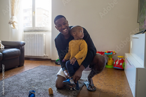 Valokuvatapetti Father sitting on the floor at home putting on shoes on his baby toddler - Singl