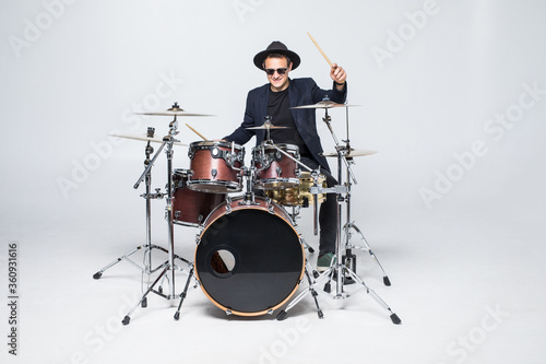 Young man in a suit playing drums isolated on white background Canvas Print